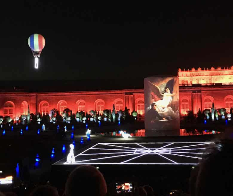 Illuminated characters and visual effects at Chateau de Versailles spectacle.